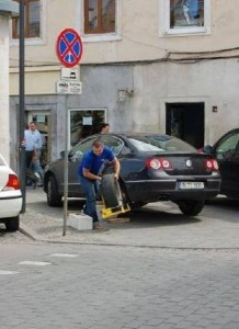водитель фольцвагена снимает блокиратор колес